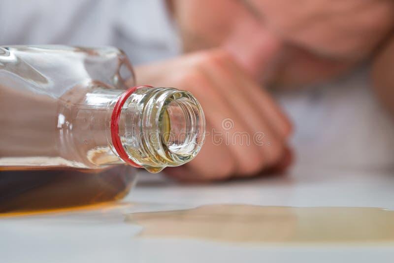 Berusad man med en flaska av starksprit royaltyfria bilder