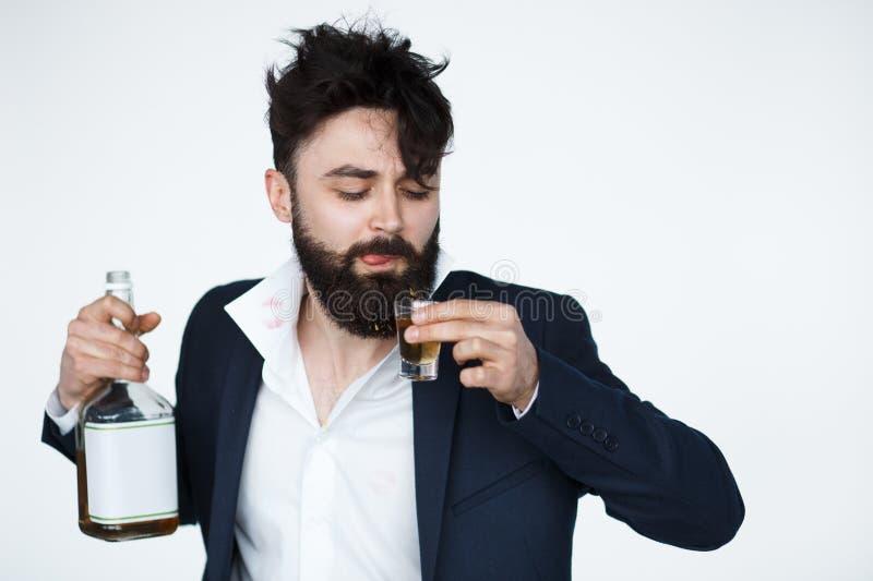 Berusad man som dricker ett exponeringsglas av alkoholdrycken royaltyfri fotografi