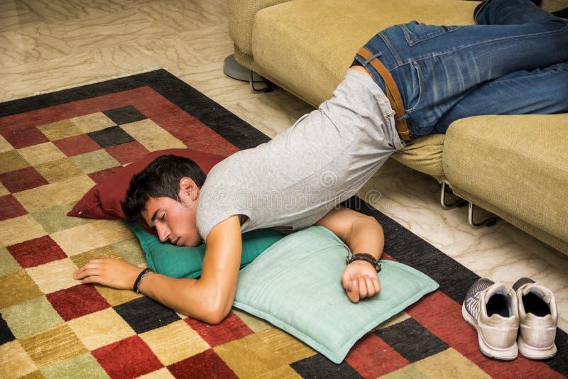 Berusad man som vilar på soffan med huvudet på golvet arkivfoto
