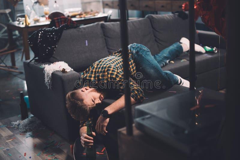 Berusad skäggig hållande ölflaska för ung man som ligger på soffan i smutsigt rum arkivfoton