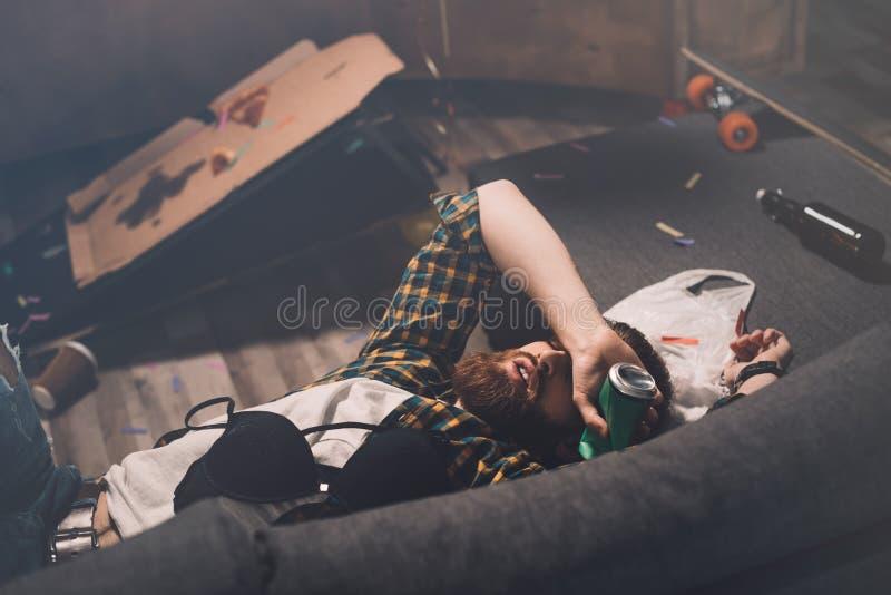 Berusad skäggig ung man som sover på soffan med behån och ölburken fotografering för bildbyråer