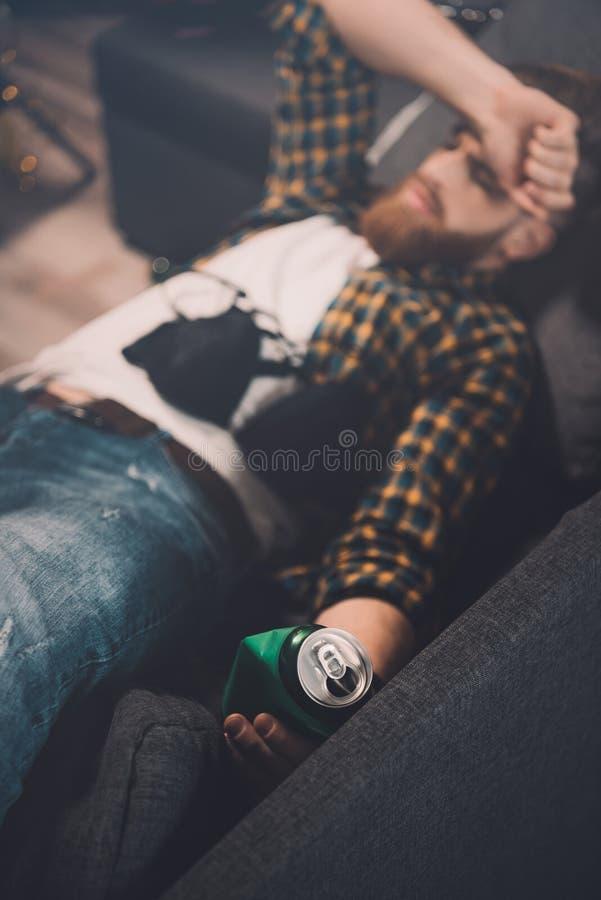 Berusad skäggig ung man som sover på soffan med behån och ölburken arkivbild