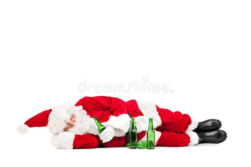 Berusade Santa Claus som ligger på jordningen fotografering för bildbyråer