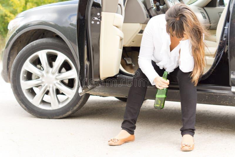 Berusat kvinnasammanträde i dörren av hennes bil fotografering för bildbyråer