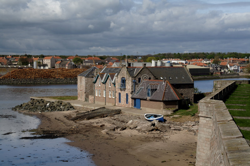 Berwick Ramparts. A house just outside the protection of the ramparts, with the docks and wood pile in teh background royalty free stock photos