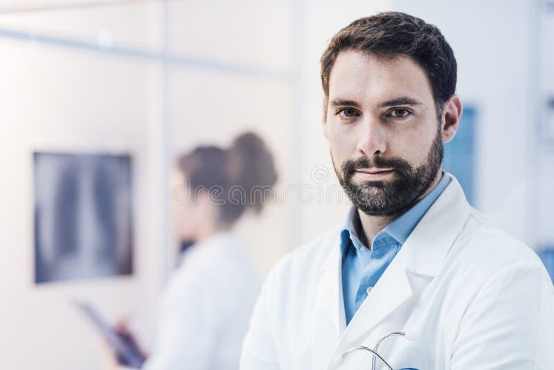?berzeugter Doktor, der im B?ro aufwirft stockfotografie