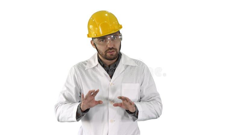 ?berzeugter Ingenieur Man Talking Camera auf wei?em Hintergrund lizenzfreie stockfotos