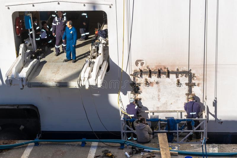 Besättning för underhåll för kryssningskepp/personal/arbetare som bär svetsande ut arbetsreparationer nära Tug Area på yttersida  royaltyfri foto