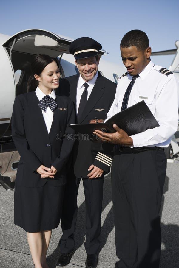Besättningsmän som diskuterar rapporter på flygfältet arkivfoton