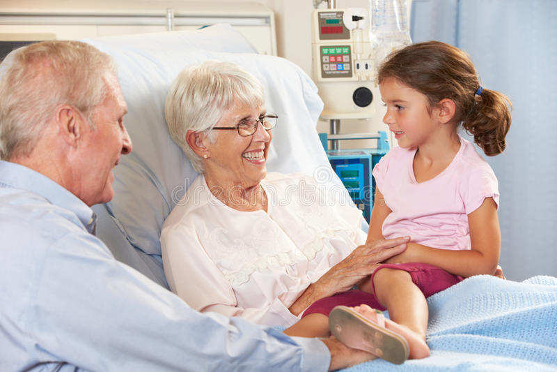 Besöka farmor för sondotter i sjukhussäng royaltyfria bilder