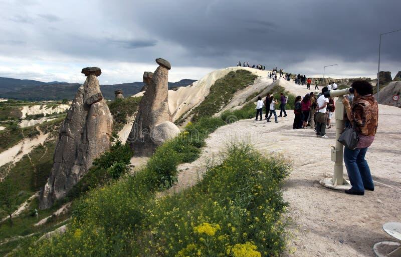 Besökare beundrar felika lampglas nära Urgup i den Cappadocia regionen av Turkiet arkivfoto