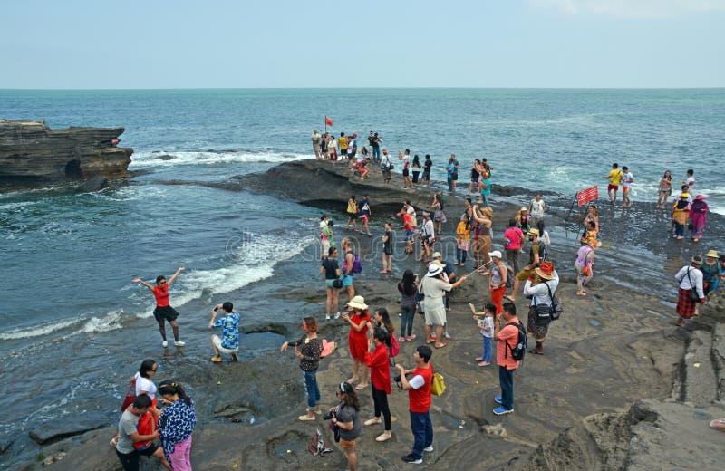 Besökare på den Tanah lotttemplet som tar foto, Bali royaltyfri fotografi