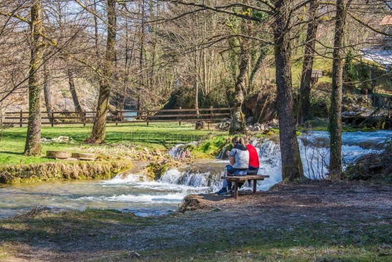 Besökare sitter i en bänk i Plitvice, Kroatien arkivbilder