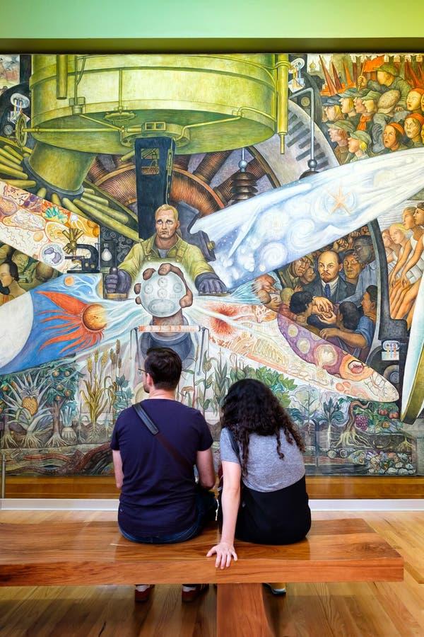 Besökare som beundrar väggmålningarna av Diego Rivera på Palacioen de Bellas Artes i Mexico - stad arkivfoton