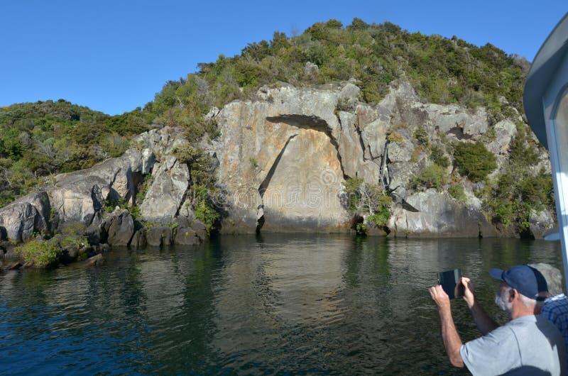 Besökare som fotograferar den iconic Maori Rock Carving på sjöTau royaltyfri fotografi