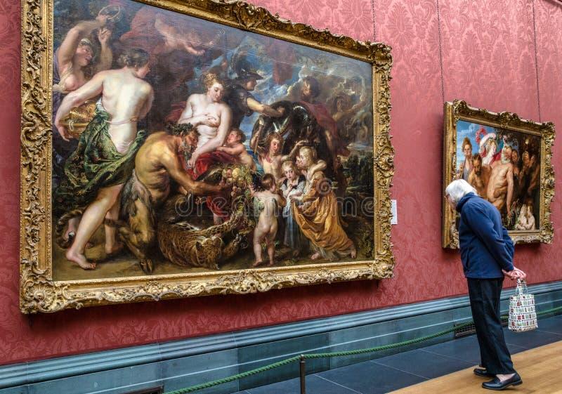 Besökare som ser målning i nationell galleryin London arkivfoto