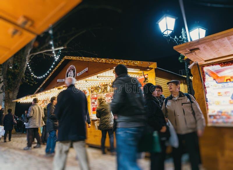 Besökare som shoppar den lyckliga beundra julmarknaden arkivbild