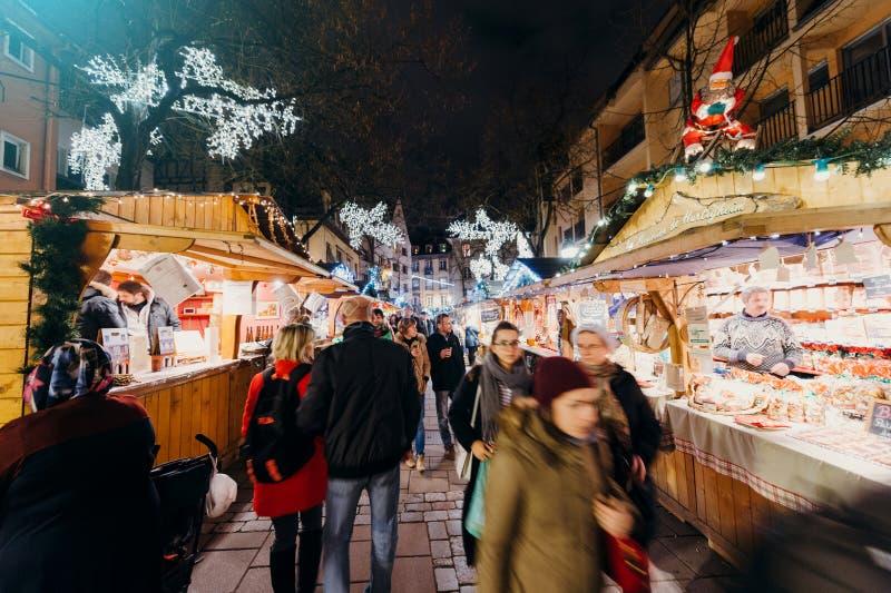 Besökare som shoppar den lyckliga beundra julmarknaden fotografering för bildbyråer