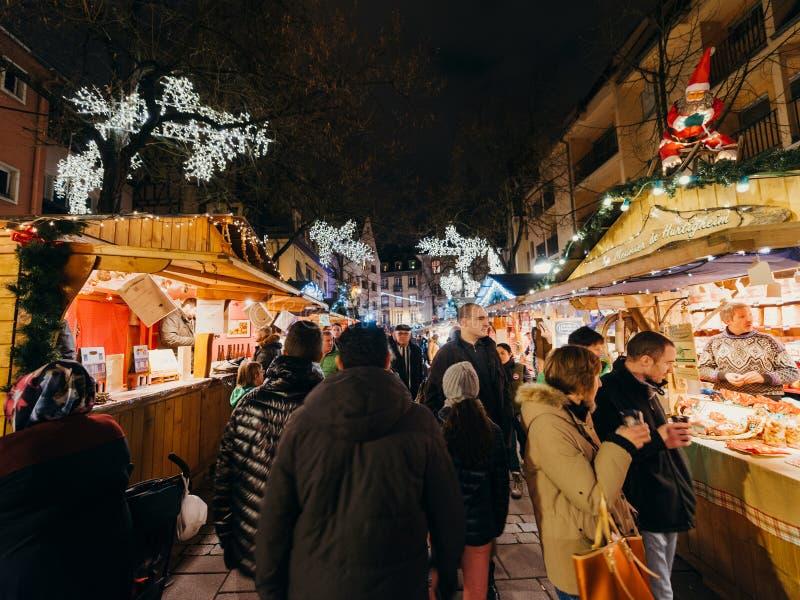 Besökare som shoppar den lyckliga beundra julmarknaden royaltyfria bilder