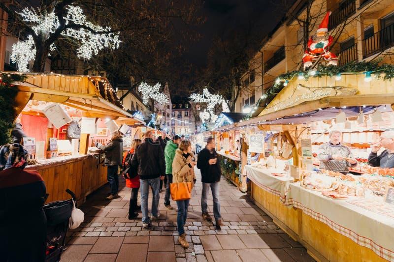 Besökare som shoppar den lyckliga beundra julmarknaden arkivfoton