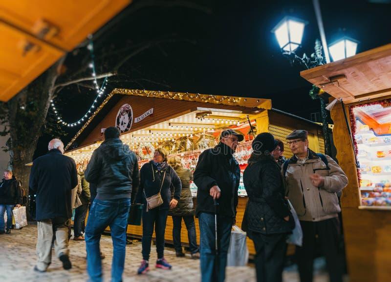 Besökare som shoppar den lyckliga beundra julmarknaden arkivfoto