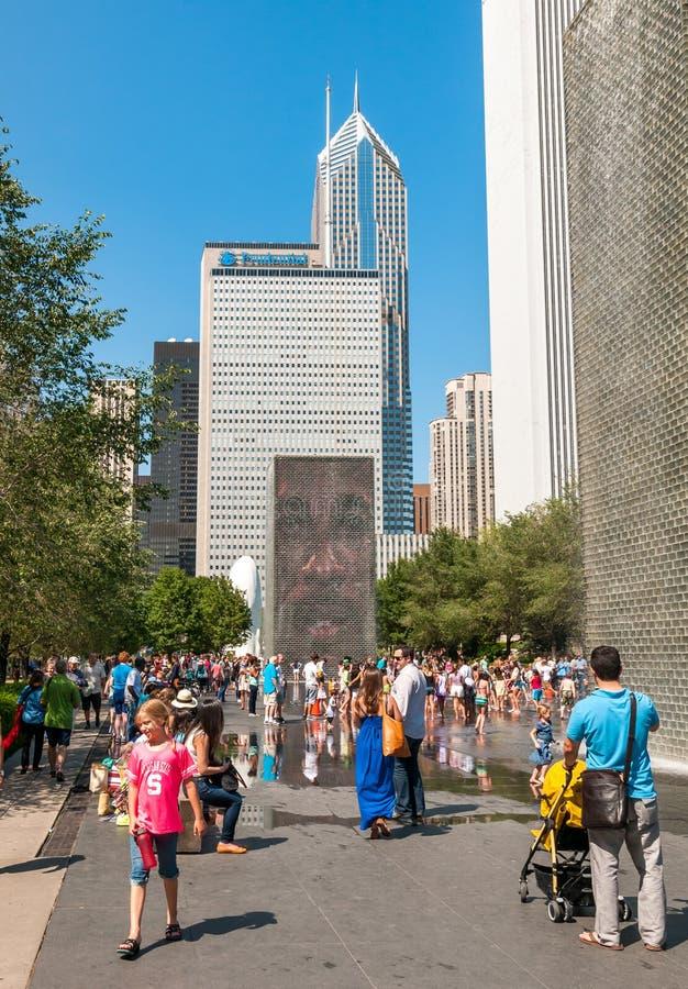 Besökare som tycker om den populära kronaspringbrunnen i millenium, parkerar på en varm sommardag i det Chicago centret arkivfoton