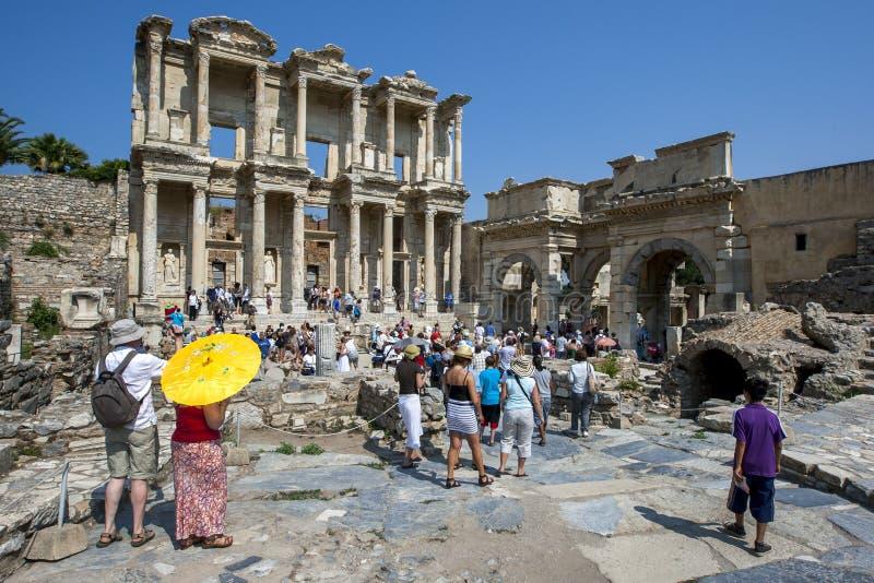Besökare till Ephesus nära Selcuk i Turkiet tränger ihop runt om fördärvar av arkivet av Celcus royaltyfri bild