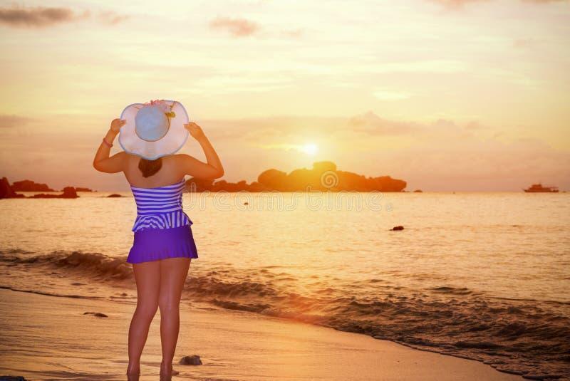 Besökarekvinna som ser soluppgången över havet royaltyfria foton