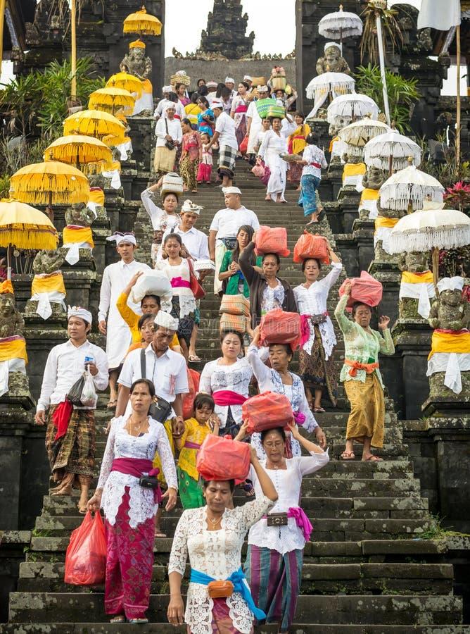 Besakih, Bali/Indonesia - 9 de abril de 2015: Un grupo de decend hindú de la gente del Balinese las escaleras del templo de Besak fotos de archivo libres de regalías