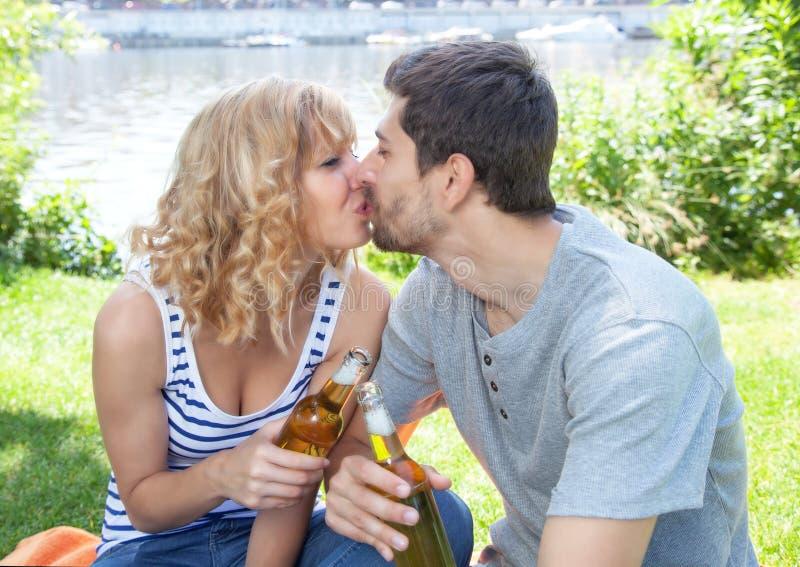 Besando pares en un partido afuera imágenes de archivo libres de regalías