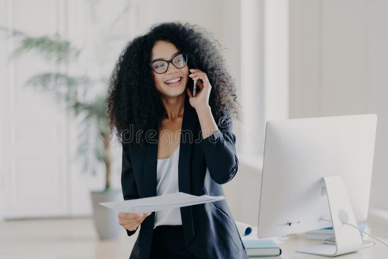 Besbeschäftigt weibliche Geschäftsführerin hält das Handy in Ohr, hält Unterlagen, Schecks Bericht, hat Telefongespräche, trägt B stockfotos