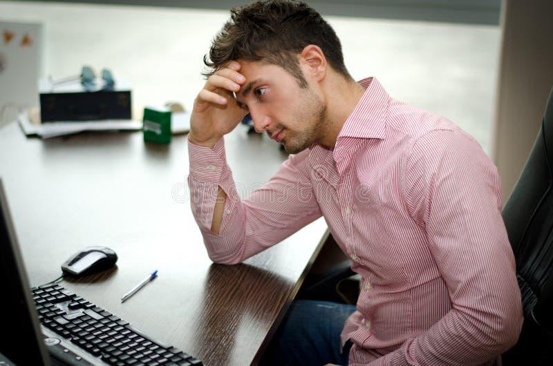 Beschäftigte, besorgte junge männliche Arbeitskraft, die entlang des Computers anstarrt stockbilder