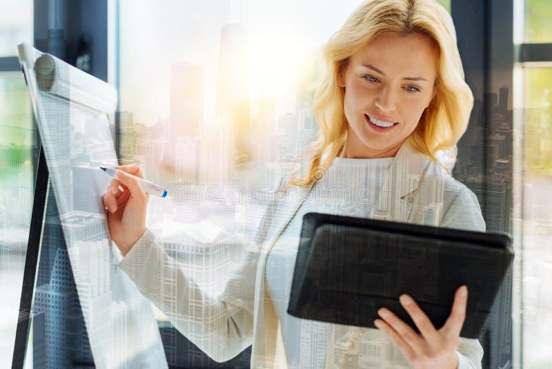 Beschäftigte Frau, die ein Brett und eine Tablette verwendet stockfoto