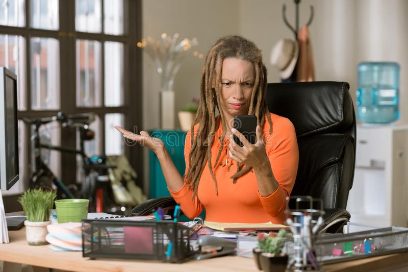 Besch?ftigte Frau mit Drealocks, das reagiert, um an ihrem Telefon zufriedenzustellen lizenzfreie stockfotos