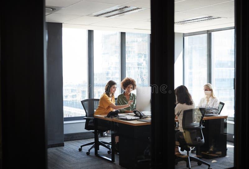 Beschäftigte Funktion von vier weiblichen kreativen Kollegen in einem Büro, gesehene durch Glaswand mit Text auf ihm stockfoto