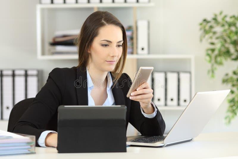 Beschäftigte Geschäftsfrau, die mehrfache Geräte im Büro verwendet lizenzfreies stockfoto