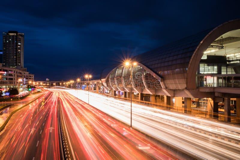 Beschäftigte Landstraße nahe bei dem Bahnhof während der Nachtzeit lizenzfreie stockfotos