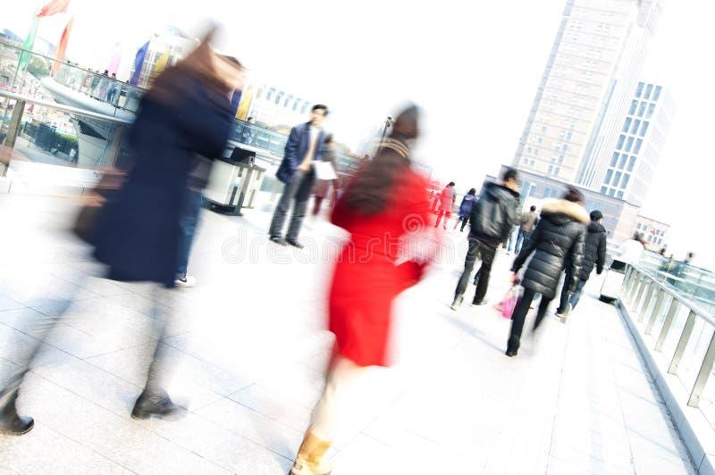 Beschäftigte Leute, die in eine Stadt mit unscharfem Effekt gehen stockfoto