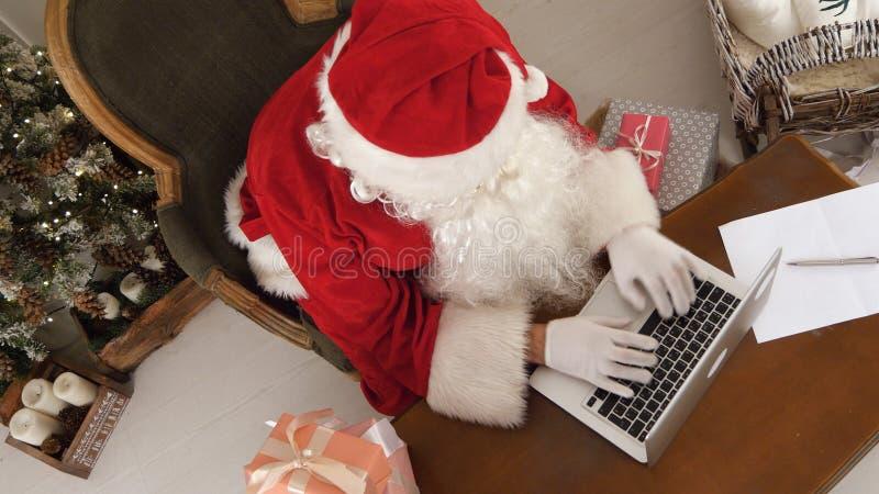 Beschäftigte Santa Claus, die eine Liste von den Geschenken auf seinem Laptop macht lizenzfreies stockfoto
