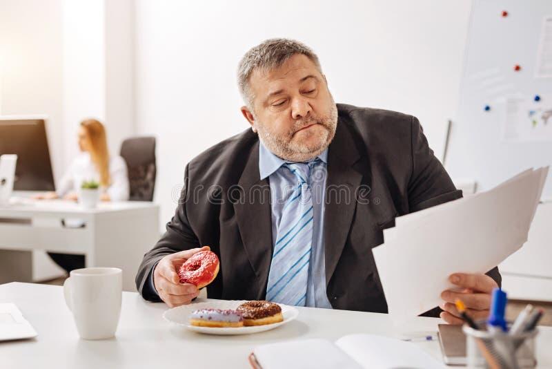 Beschäftigter engagierter Angestellter, der an seinem Arbeitsplatz isst lizenzfreie stockfotografie