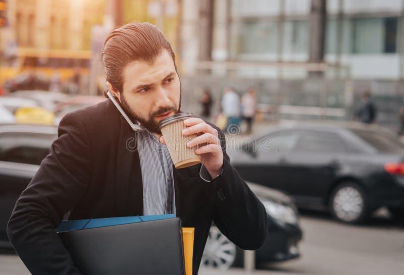 Beschäftigter Mann ist in Eile, er hat nicht Zeit, er wird den unterwegssnack essen Essende Arbeitskraft, trinkender Kaffee stockfotografie