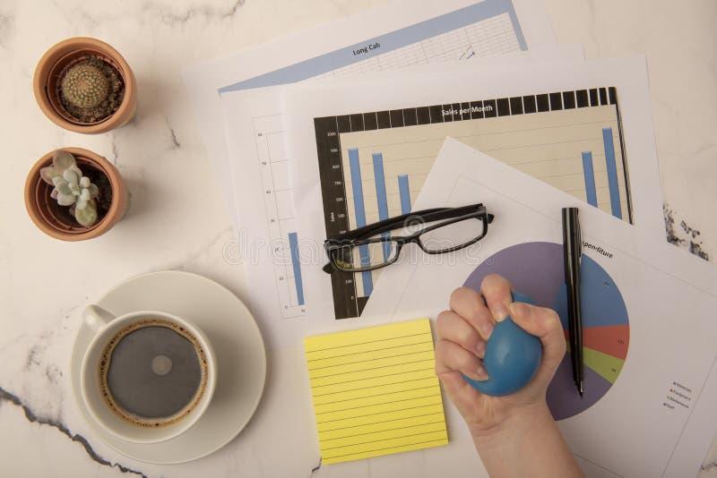 Beschäftigter Schreibtisch mit der Hand, die Druckball zusammendrückt lizenzfreie stockfotos