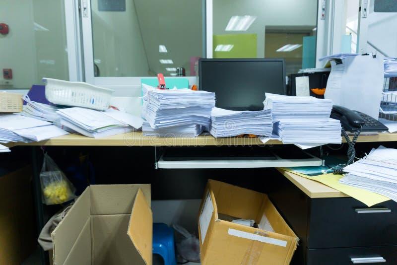 Beschäftigter, unordentlicher und durcheinandergeworfener Arbeitsplatz, voll von den Dokumenten stockbild