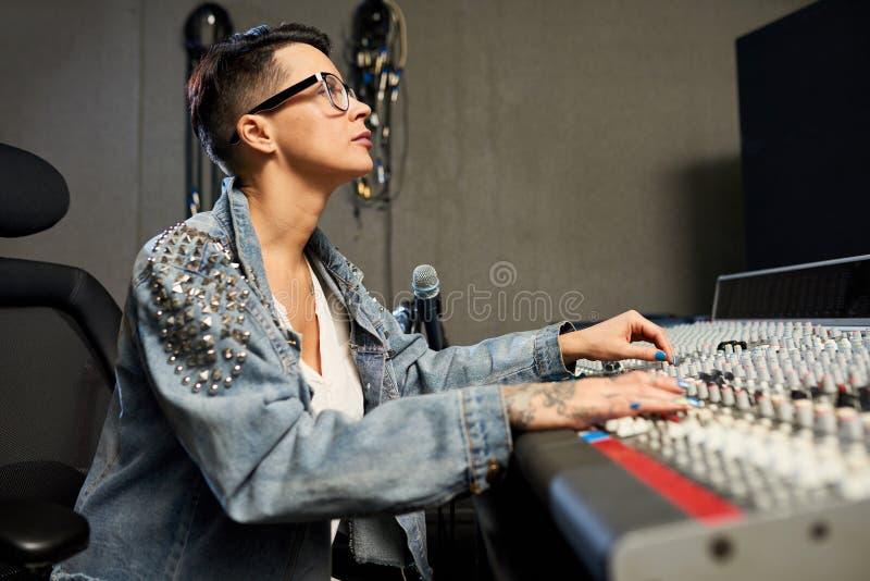 Beschäftigter weiblicher Audioingenieur, der im Tonstudio arbeitet lizenzfreies stockbild