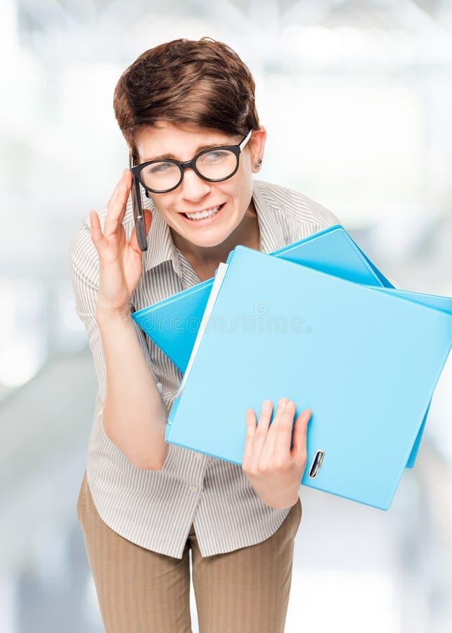 Beschäftigtes Arbeiten des Büroangestellten mit Ordnern und Telefon stockfotos