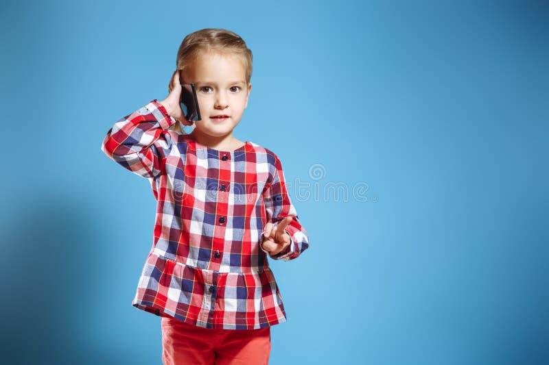 Beschäftigtes kleines Mädchen, das am Handy auf blauem Hintergrund spricht lizenzfreie stockfotografie