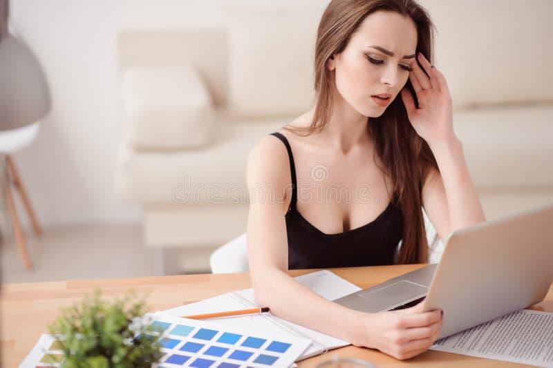 Beschäftigtes Mädchen, das am Tisch arbeitet stockfotografie