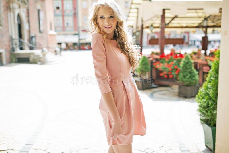 Beschämte Blondine, die rosa Kleid tragen stockfoto