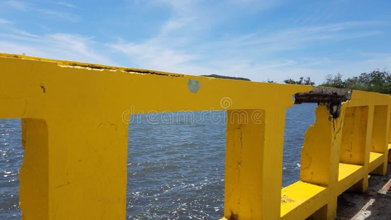 Beschadigd geel cementtraliewerk met metaalbar en water in Guanica, Puerto Rico stock fotografie