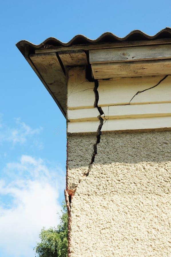 Beschadigde de muurhoek van de huisgipspleister Gebarsten Muur dichtbij Dakbouw het detail van beschadigde huishoek dilapidated d royalty-vrije stock afbeelding